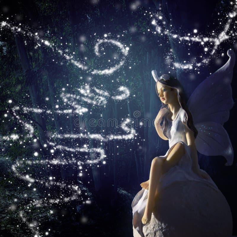 wizerunek magiczna mała czarodziejka w lasowym obsiadaniu nad kamieniem zdjęcie stock
