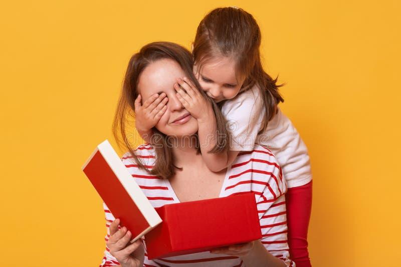Wizerunek mali śliczni córki przymknięcia oczy mamusia, kobiety mienia prezenta czerwony pudełko podczas gdy siedzący na podłogow zdjęcie royalty free