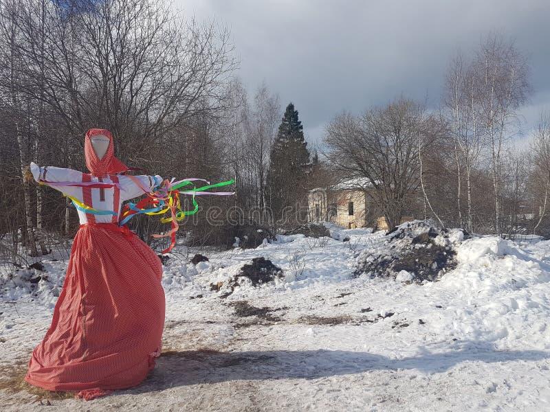 Wizerunek Maslenitsa w Rosyjskim ludowym kostiumu pali w śniegu podczas tradycyjnego święta narodowego macierzysty pożegnanie obraz royalty free