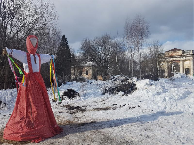 Wizerunek Maslenitsa w Rosyjskim ludowym kostiumu pali w śniegu podczas tradycyjnego święta narodowego macierzysty pożegnanie obrazy royalty free