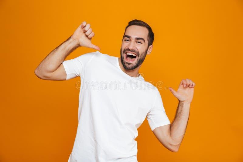 Wizerunek odizolowywający nad żółtym tłem atrakcyjny facet 30s w koszulce wskazuje palce przy on podczas gdy stojący, obraz stock
