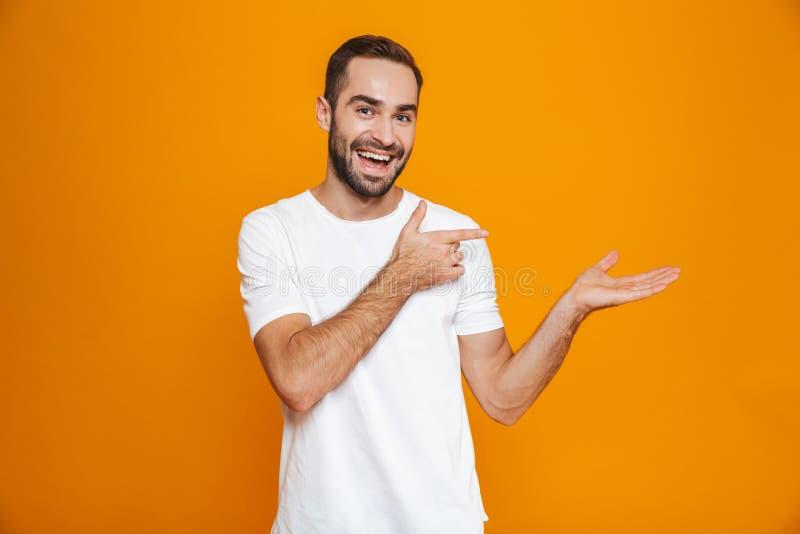 Wizerunek odizolowywający nad żółtym tłem optymistycznie mężczyzna 30s z brodą i wąsy pokazuje copyspace na palmie podczas gdy st fotografia royalty free