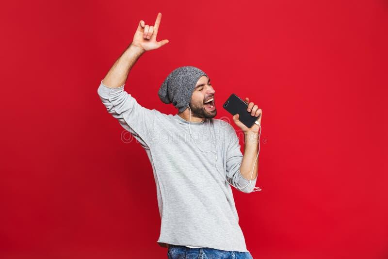 Wizerunek odizolowywający nad czerwonym tłem optymistycznie mężczyzny 30s śpiew podczas gdy słuchający muzyka z słuchawkami i tel zdjęcia stock