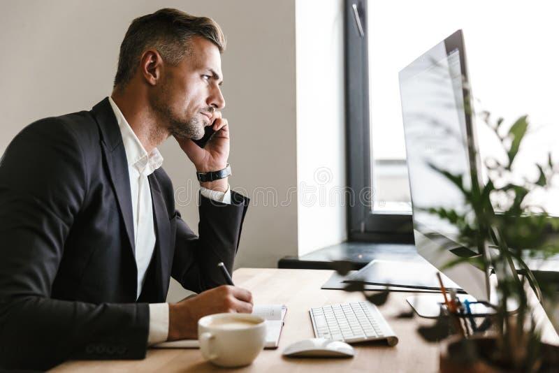 Wizerunek opowiada na telefonie komórkowym pomyślny biznesmen podczas gdy pracujący na komputerze w biurze zdjęcie stock
