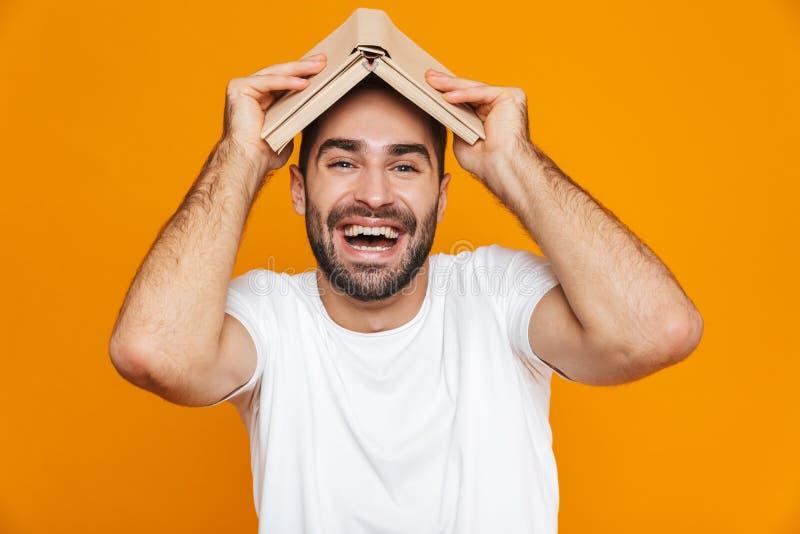Wizerunek optymistycznie mężczyzna 30s w białej koszulce trzyma książkę na jego głowie nad żółtym tłem, obraz royalty free