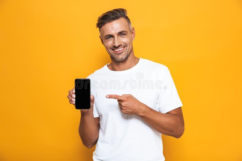 Wizerunek optymistycznie mężczyzna 30s w biali koszulki ono uśmiecha się areszt przy sądzie telefonie i podczas gdy stać odizolow zdjęcie stock