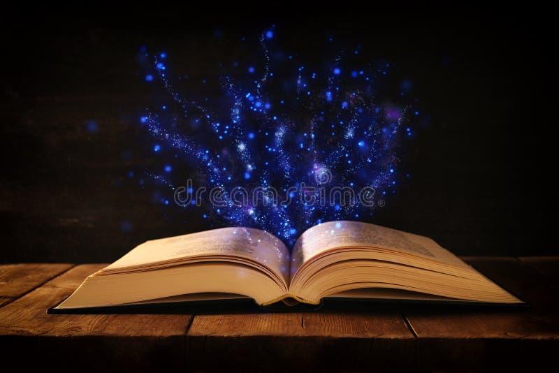 wizerunek otwarta antyk książka na drewnianym stole z błyskotliwości narzutą zdjęcie royalty free
