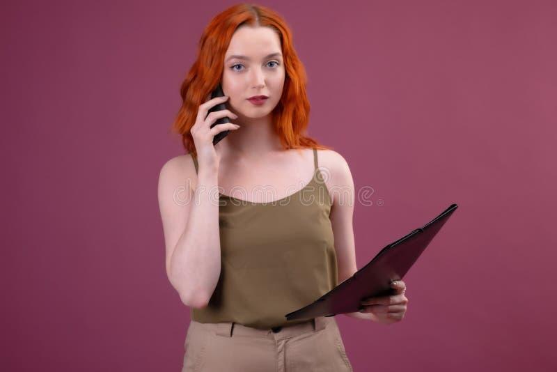 Wizerunek piękna zadziwiająca rudzielec kobieta pozuje nad różową tła mienia falcówką opowiada telefonem komórkowym zdjęcia stock