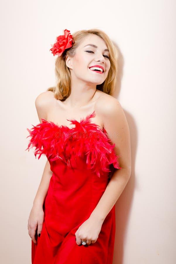 Wizerunek pięknej splendoru pinup młodej blond kobiety szczęśliwy ono uśmiecha się w czerwieni sukni z kwiatem w jej włosy na biał zdjęcia royalty free