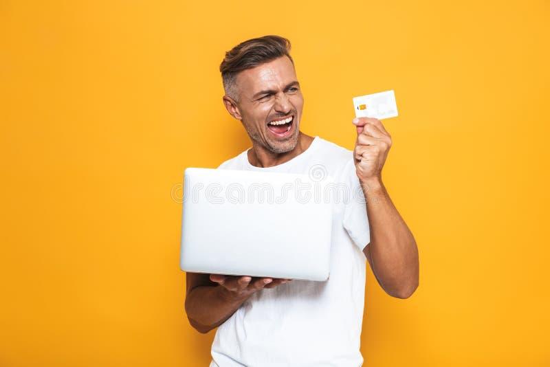 Wizerunek piękny facet 30s w białej koszulki mienia srebra karcie kredytowej i laptopie zdjęcia stock
