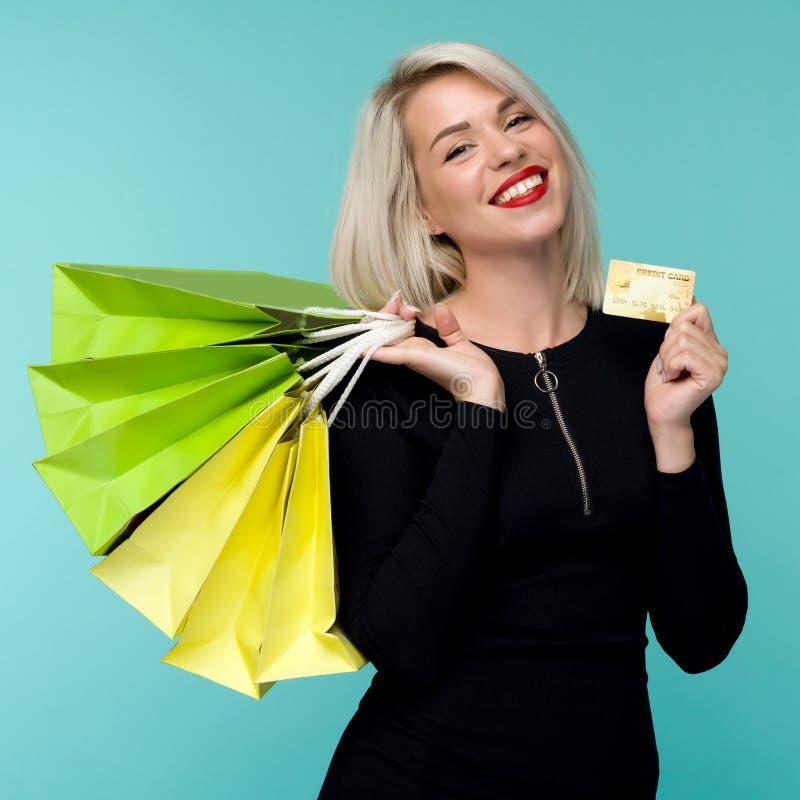 Wizerunek piękny szczęśliwy młody blondynki kobiety pozować odizolowywam nad błękit ściany tła mienia torbami na zakupy zdjęcia stock