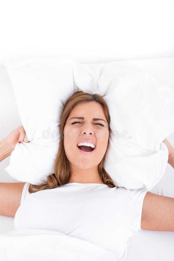 Wizerunek podrażniony żeński lying on the beach na łóżku i przymknięciu jej ucho z fotografia stock