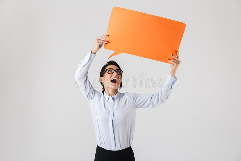 Wizerunek pomyślna biurowa kobieta jest ubranym eyeglasses trzyma żółtego copyspace plakat, odizolowywający nad białym tłem obraz royalty free