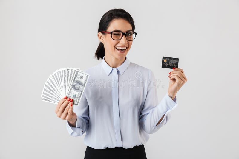 Wizerunek pomyślna biurowa kobieta jest ubranym eyeglasses trzyma wiązkę pieniądze i karta kredytowa, odizolowywającą nad białym  obrazy stock
