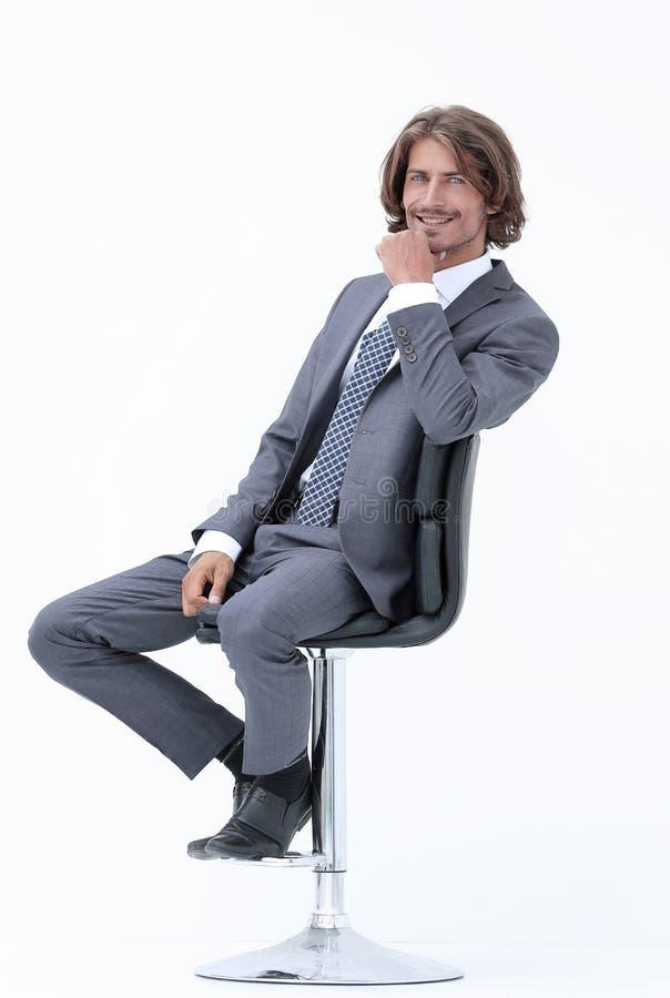 Wizerunek pomyślny biznesmen w eleganckim kostiumu sadzającym na krześle obraz royalty free