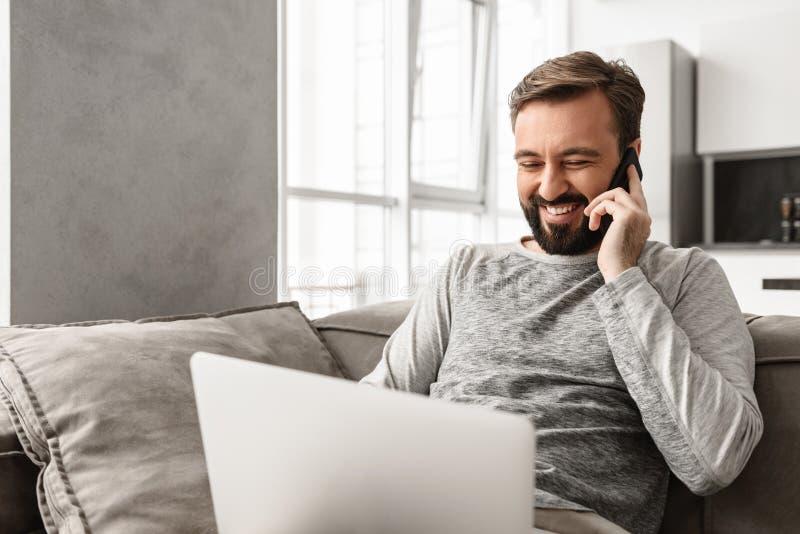 Wizerunek pozytywny mężczyzna 30s w przypadkowej odzieży obsiadaniu na kanapie w livi zdjęcia royalty free
