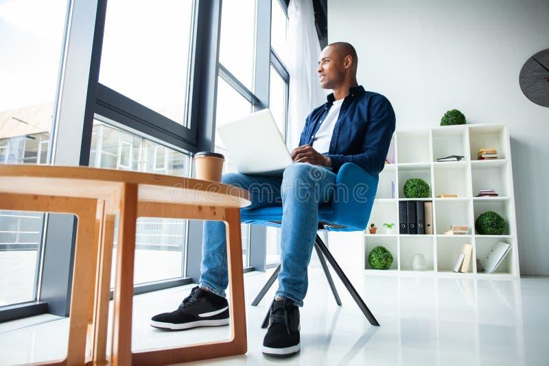 Wizerunek pracuje na jego laptopie amerykanina afrykańskiego pochodzenia biznesmen Przystojny młody człowiek przy jego biurkiem obraz royalty free