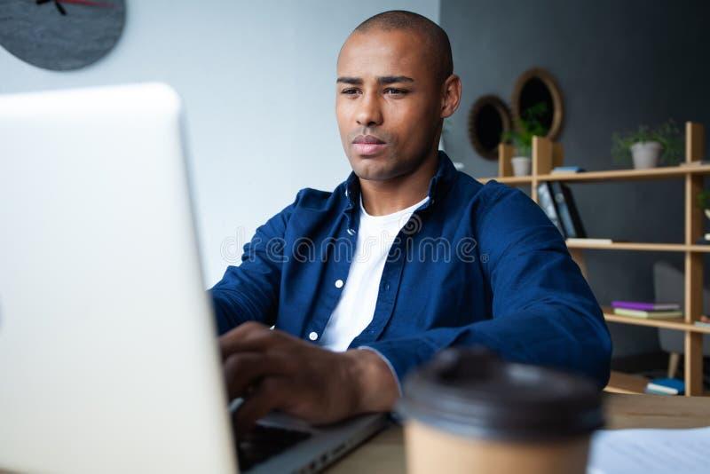 Wizerunek pracuje na jego laptopie amerykanina afrykańskiego pochodzenia biznesmen Przystojny młody człowiek przy jego biurkiem zdjęcie stock