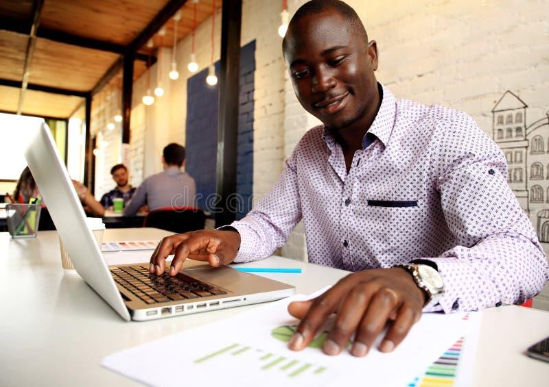 Wizerunek pracuje na jego laptopie amerykanina afrykańskiego pochodzenia biznesmen Przystojny młody człowiek przy jego biurkiem fotografia stock