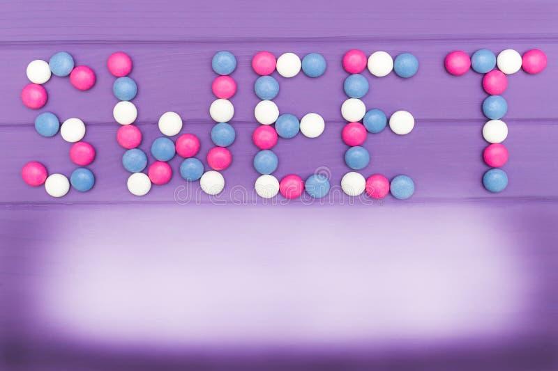 Wizerunek robić kolorowi cukierki na fiołkowym tle słowo cukierki zdjęcia royalty free