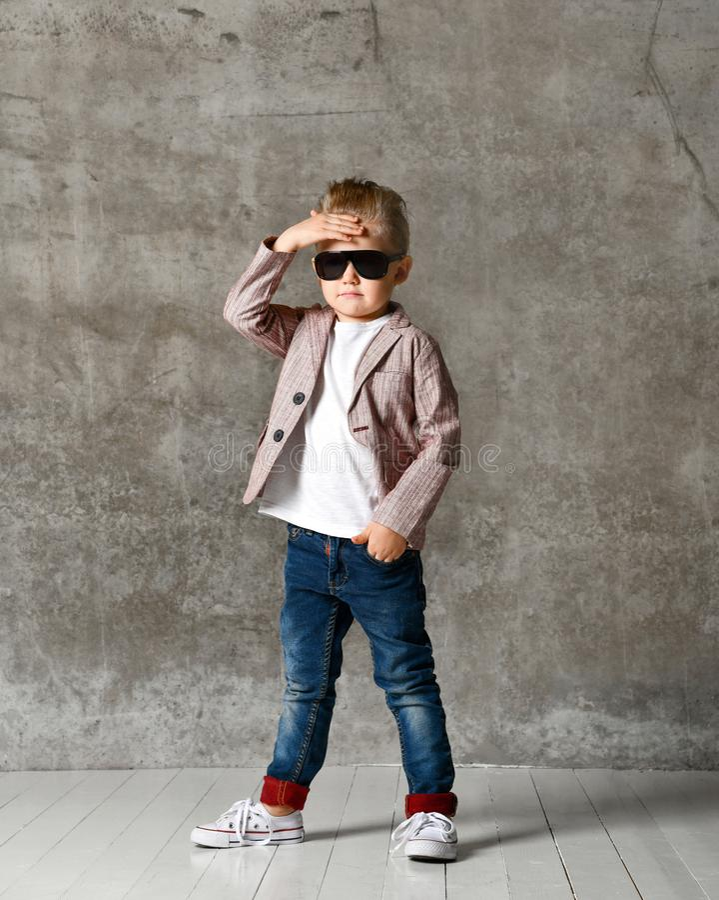 Wizerunek rozochocona z podnieceniem chłopiec dziecka pozycja odizolowywająca nad betonową ścianą obrazy royalty free