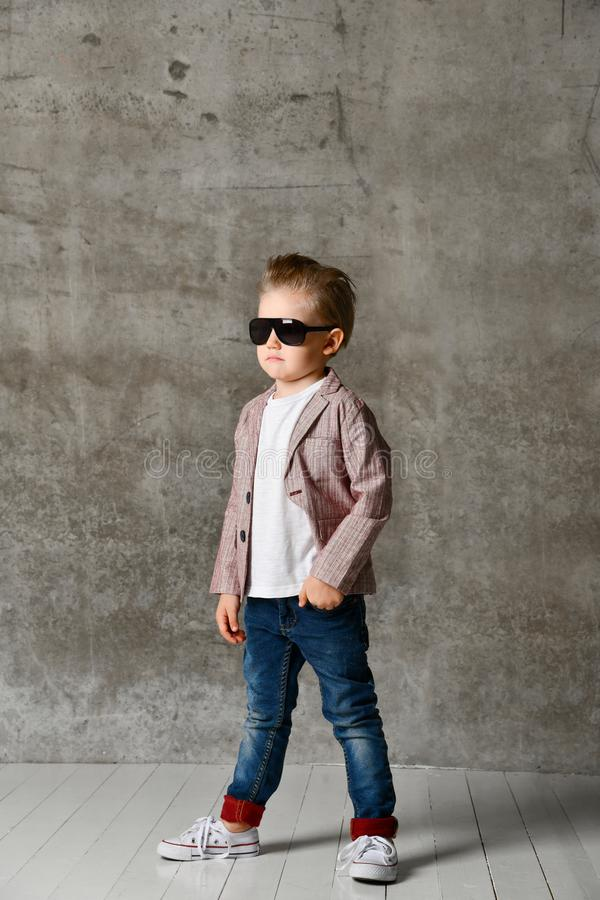 Wizerunek rozochocony z podnieceniem chłopiec dziecko stoi nad betonową ścianą zdjęcia stock
