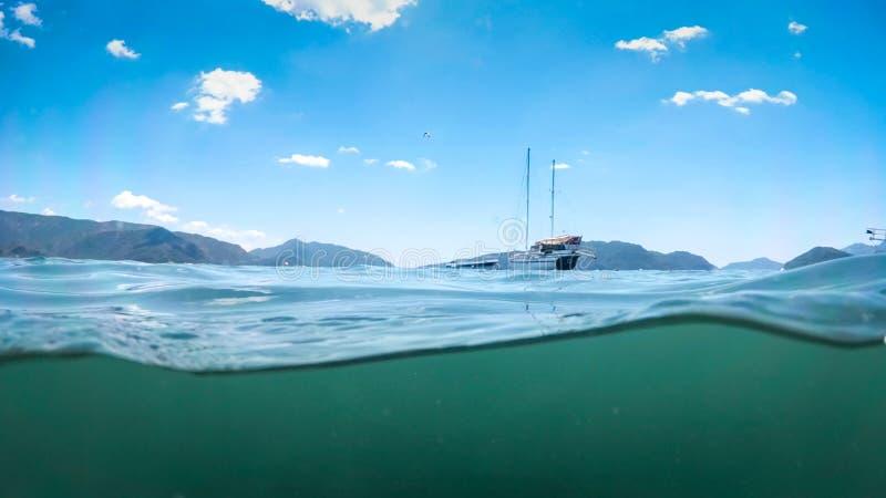 Wizerunek spod wody jacht w morzu przeciw pi?knym g?rom obraz stock
