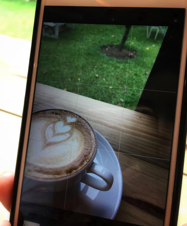 Wizerunek strzelanina w telefonie gorąca cappuccino kawa w białej filiżanki i spodeczka miękkiej ostrości na drewnianym stołowym  obrazy royalty free