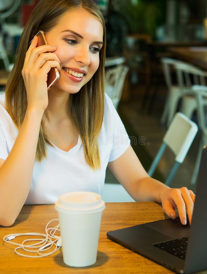 Wizerunek szczęśliwa kobieta używa laptop i smartphone w kawiarni Lifest obraz stock