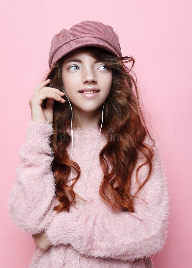 Wizerunek szczęśliwa nastoletnia dziewczyny pozycja odizolowywająca na różowym tle w różowym kapeluszu i pulowerze, obraz stock