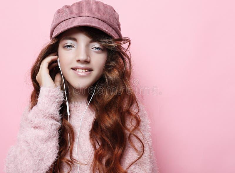 Wizerunek szczęśliwa nastoletnia dziewczyny pozycja odizolowywająca na różowym tle w różowym kapeluszu i pulowerze, Styl życia i  fotografia stock