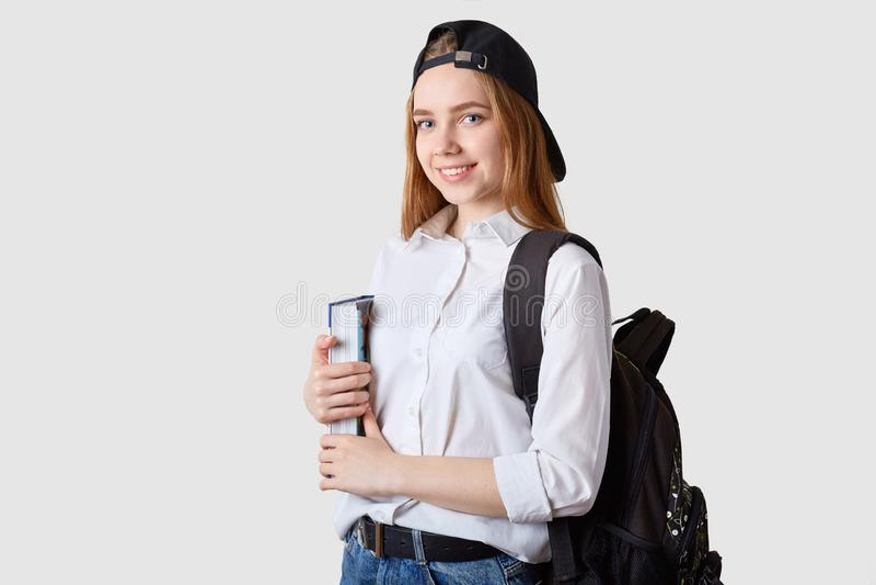Wizerunek szczęśliwy Kaukaski uczeń z plecakiem i dużą książką, ubierająca koszula, cajgu naliczka nakrętka z powrotem, stoi ono  obraz royalty free