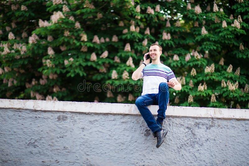 Wizerunek szczęśliwy młodego człowieka odprowadzenie na ulicie podczas gdy opowiadający jego telefonem zdjęcia stock