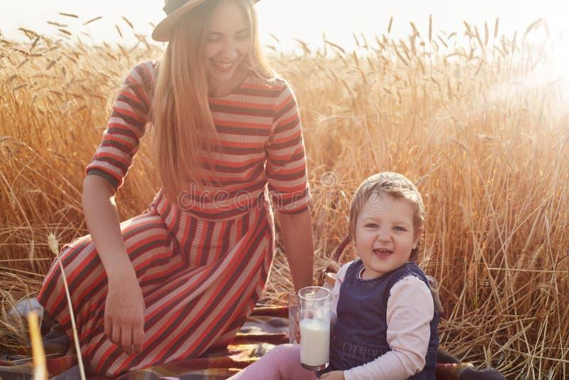 Wizerunek szczęśliwy rozochocony dziecięcy patrzeć bezpośrednio przy kamerą, trzyma szkło mleko w jeden ręce, być szczęśliwy Uśmi fotografia stock