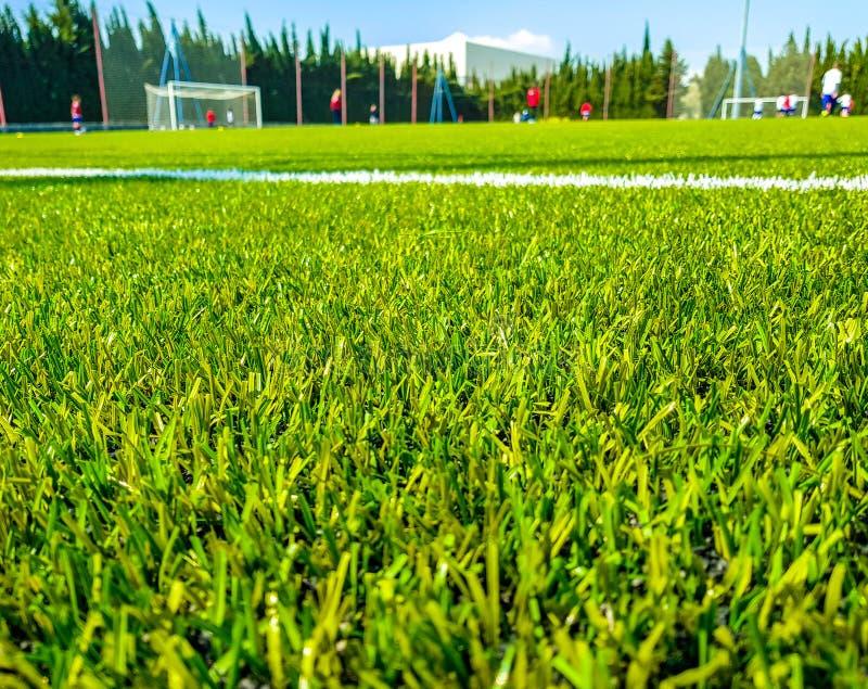 Wizerunek sztuczna trawa w tle dzieci bawić się piłkę nożną i przedpolu fotografia royalty free