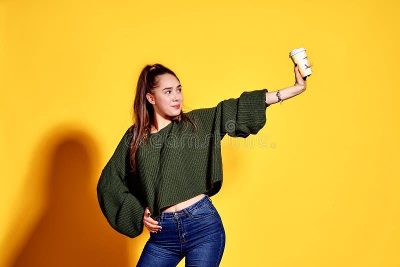 Wizerunek uśmiecha się takeaway kawę w papierowej filiżance nad żółtym tłem i trzyma ładna młoda kobieta fotografia royalty free