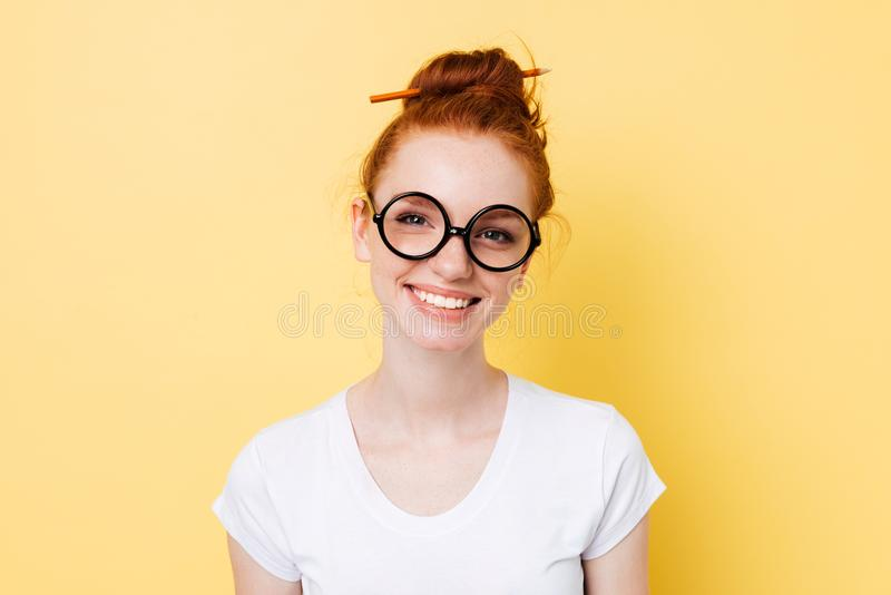 Wizerunek uśmiechnięta imbirowa kobieta patrzeje kamerę w yeglasses obrazy stock