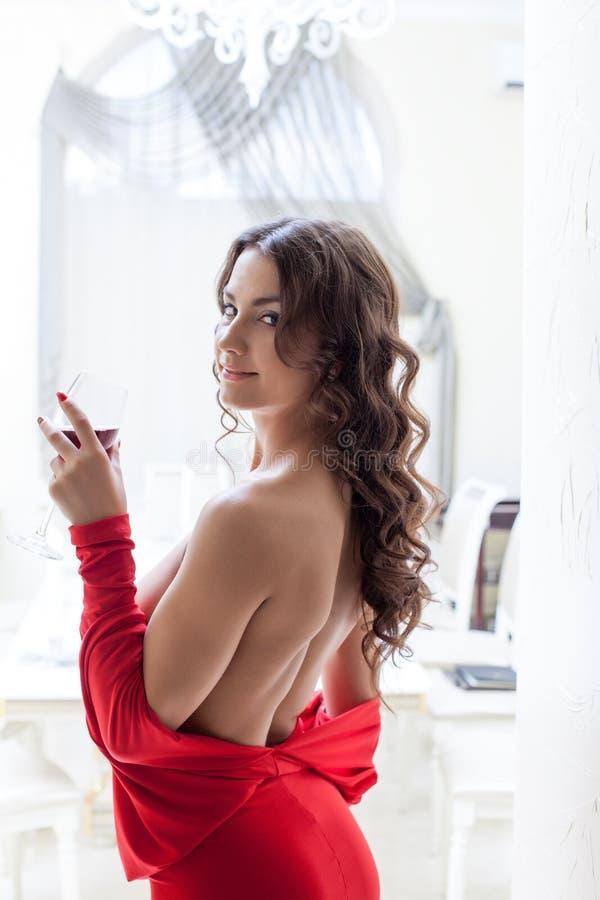 Wizerunek uśmiechnięta szczupła brunetka pozuje w czerwieni sukni obraz royalty free
