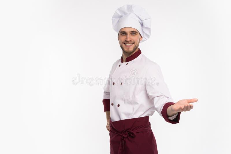 Wizerunek uśmiechnięty potomstwo kucharz w jednolitej pozycji odizolowywającej nad białym tłem Przygl?daj?cy kamery wskazywa? obraz stock