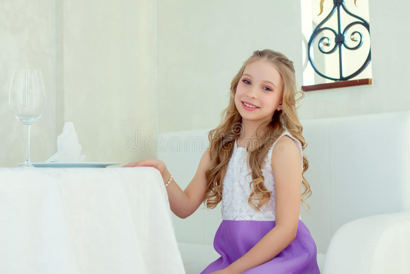 Wizerunek urocza uśmiechnięta dziewczyna pozuje przy stołem obrazy royalty free