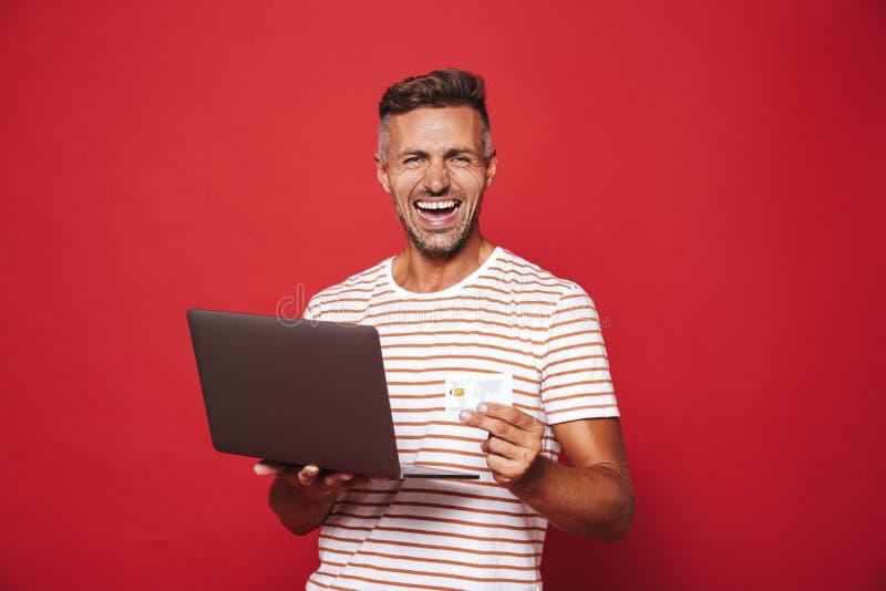 Wizerunek z podnieceniem mężczyzna ono uśmiecha się w pasiastej koszulce podczas gdy trzymający cr zdjęcia royalty free