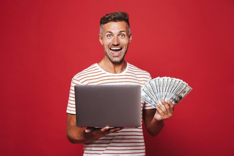 Wizerunek z podnieceniem mężczyzna ono uśmiecha się w pasiastej koszulce podczas gdy trzymający fa obraz stock