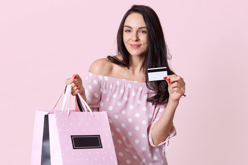 Wizerunek zadowolona młoda Europejska kobieta cieszy się zakupy na weekendzie, trzyma klingeryt kartę, torby na zakupy, wydaje pi zdjęcia stock