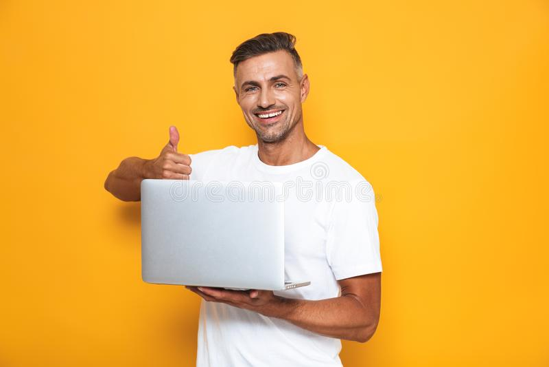 Wizerunek zarośnięty facet 30s w białym koszulki mieniu, używać srebnego laptop i obrazy royalty free