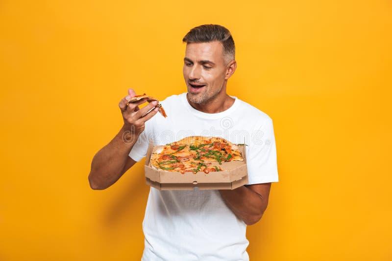 Wizerunek zarośnięty mężczyzna 30s w białym koszulki mieniu łasowanie pizzy i podczas gdy stać odizolowywam zdjęcie royalty free