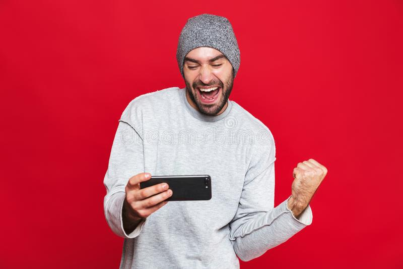 Wizerunek zarośnięty mężczyzny 30s mienia smartphone i bawić się gra wideo nad czerwonym tłem, fotografia stock