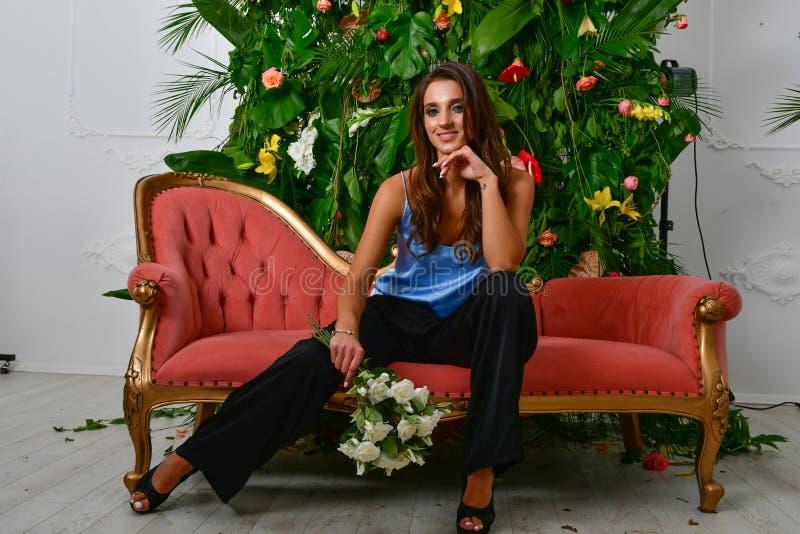 Wizerunki piękna wspaniała dziewczyna na retro czerwonej ścianie z i leżance zieleń kwiatami i liśćmi fotografia stock