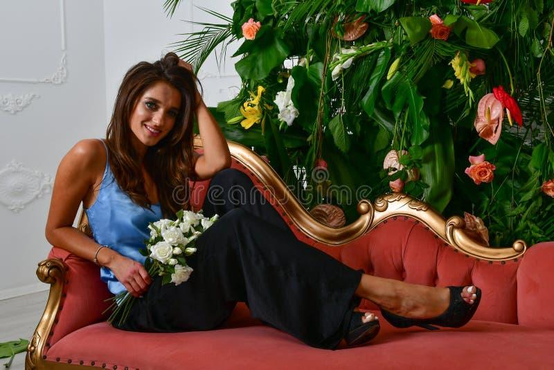 Wizerunki piękna wspaniała dziewczyna na retro czerwonej ścianie z i leżance zieleń kwiatami i liśćmi zdjęcia royalty free