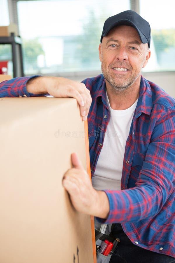 Wizerunku doręczeniowego mężczyzny mienia szczęśliwy pudełko zdjęcie royalty free