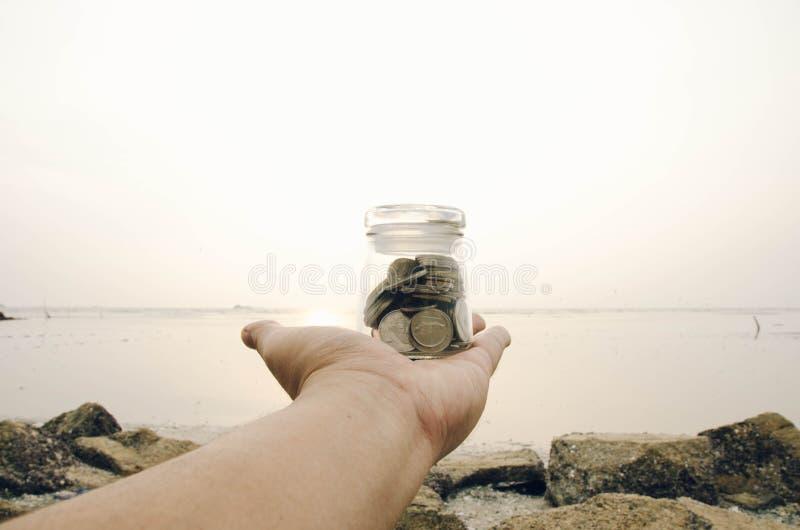 Wizerunku oszczędzania pojęcie cropped ręka trzyma szklanego słój zawierający z monetą zdjęcia royalty free